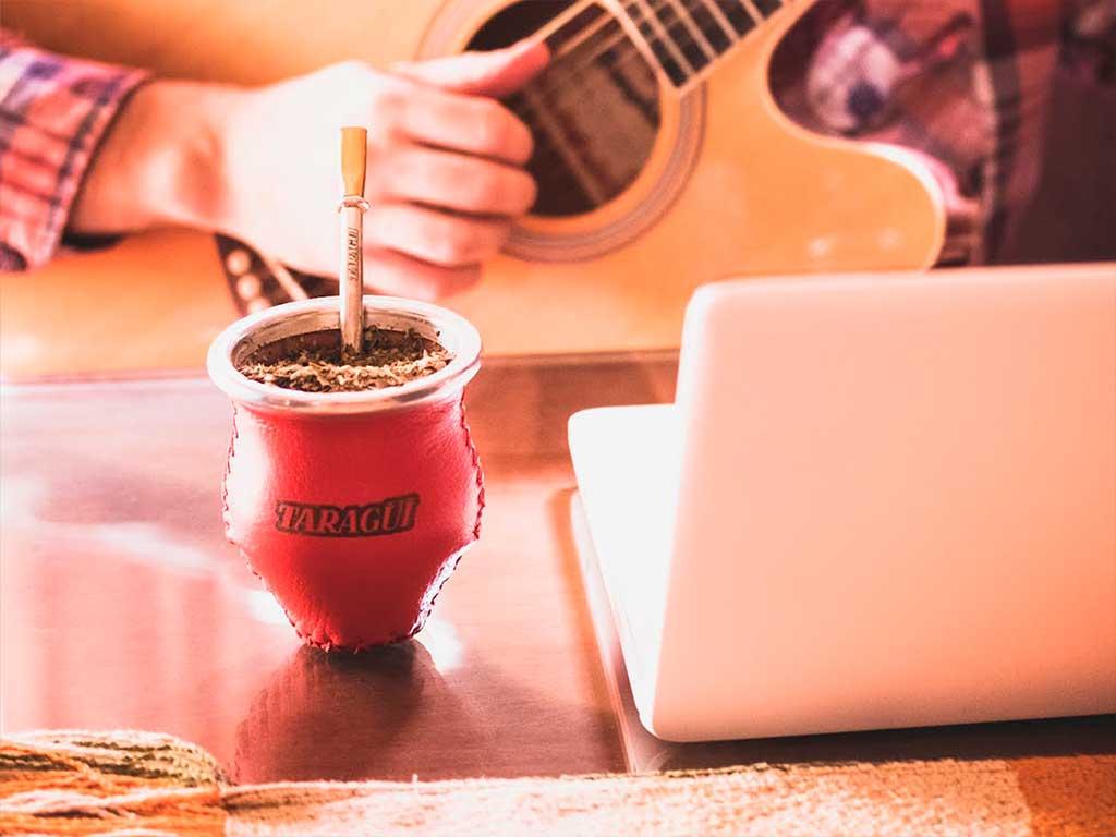 Beber, cebar o tomar Yerba Mate Taragui tocando la guitarra.